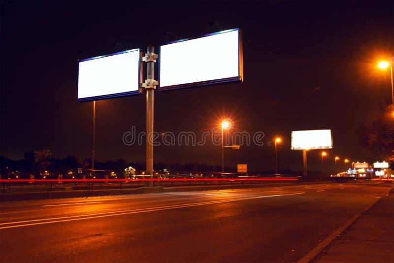 Große weiße Anschlagtafel auf Nachtstraße lizenzfreie stockbilder