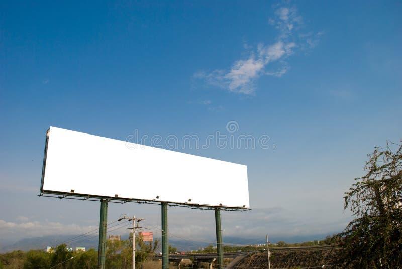 Große weiße unbelegte Anschlagtafel mit Hintergrund des blauen Himmels lizenzfreies stockbild