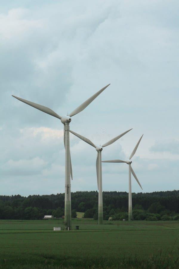 Große weiße Windmühle-Turbine auf grünem Gelände stockbild