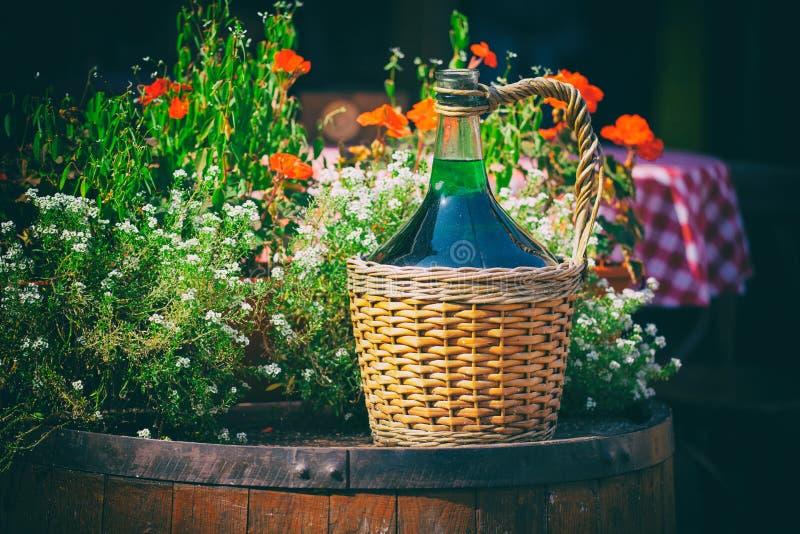 Große Weinlese-Wein-Flaschen im Weidenkorb auf einem Fass lizenzfreie stockfotos