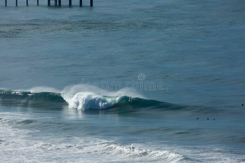 Große Welle, die mit Surfer auf Schulter bricht stockfotografie