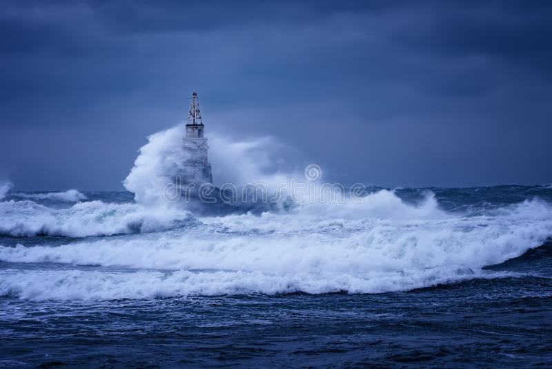 Große Welle gegen alten Leuchtturm im Hafen von Ahtopol, Schwarzes Meer, Bulgarien an einem schwermütigen stürmischen Tag Gefahr, stockbilder