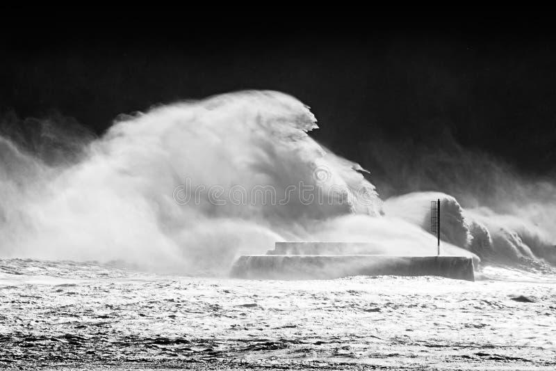 Große Wellen, die auf Wellenbrecher brechen lizenzfreie stockbilder