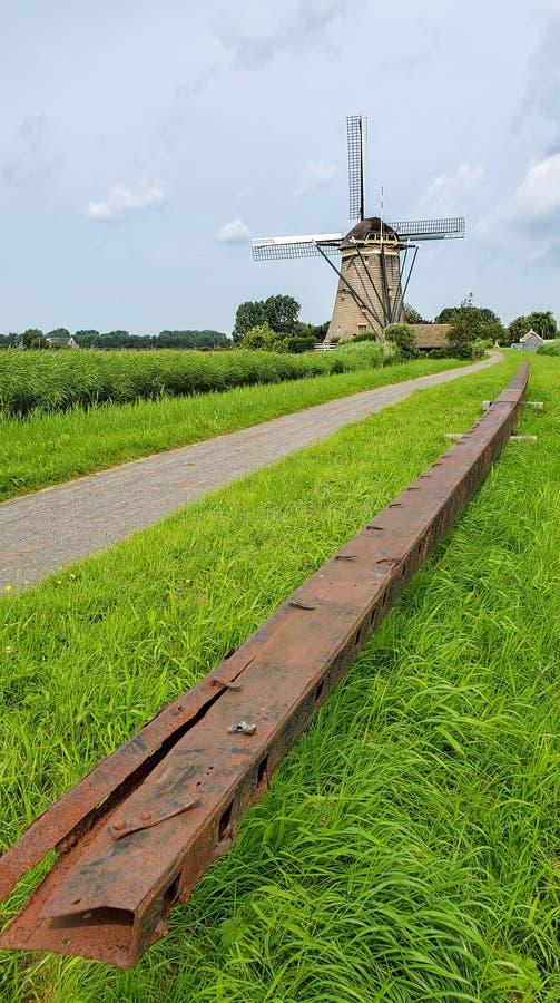 Große Windmühlensegelachse mit einer Windmühle im Hintergrund stockbild
