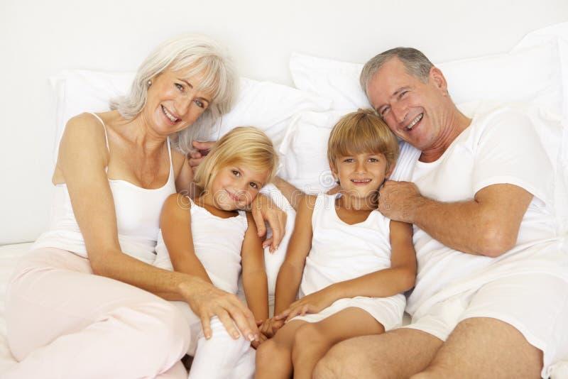 Großeltern, die auf Bett mit Enkelkindern sich entspannen stockfoto