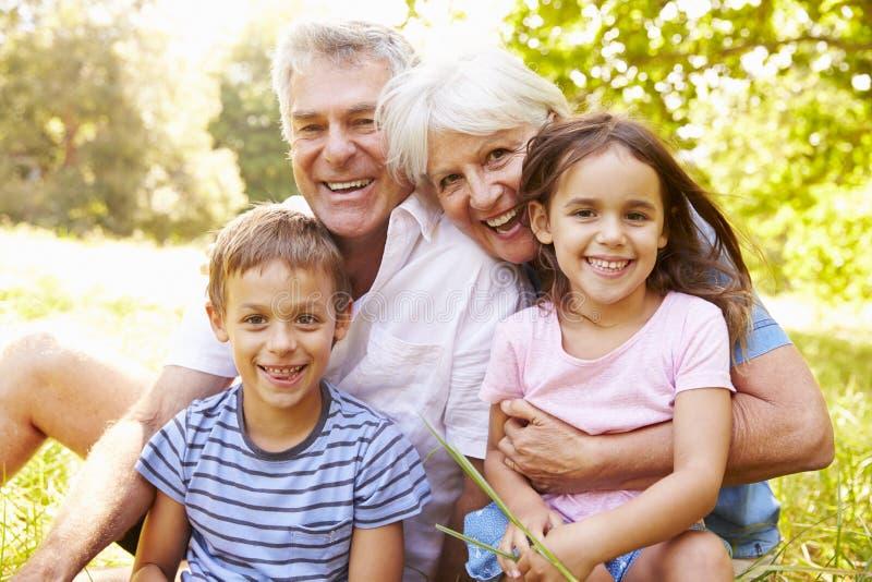 Großeltern, die draußen mit ihren Enkelkindern sitzen stockfotografie