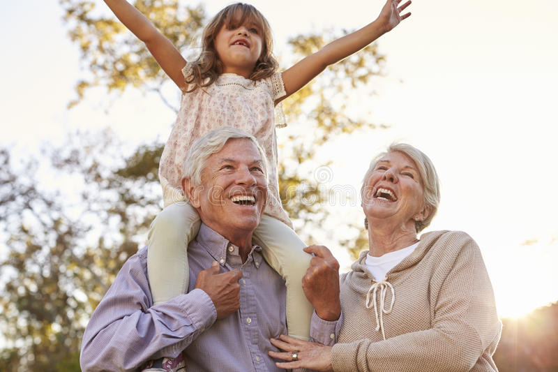 Großeltern, die Enkelin eine Schulter-Fahrt im Park geben lizenzfreie stockbilder