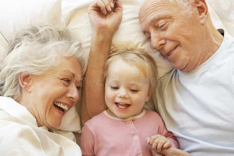 Großeltern, die Enkelin im Bett streicheln lizenzfreies stockbild