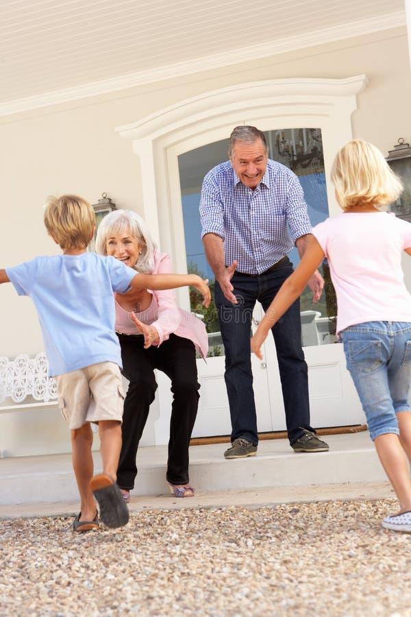 Großeltern, die Enkelkinder auf Besuch begrüßen stockbild