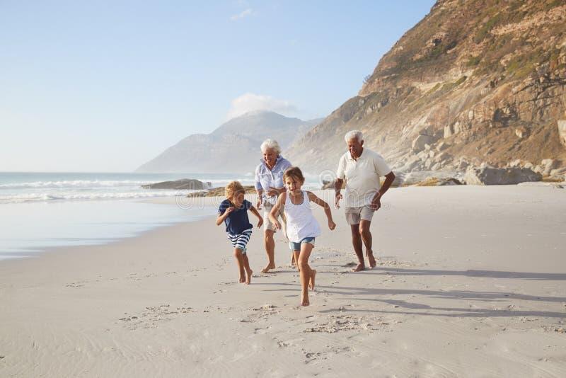 Großeltern, die entlang Strand mit Enkelkindern auf Sommer-Ferien laufen stockbild