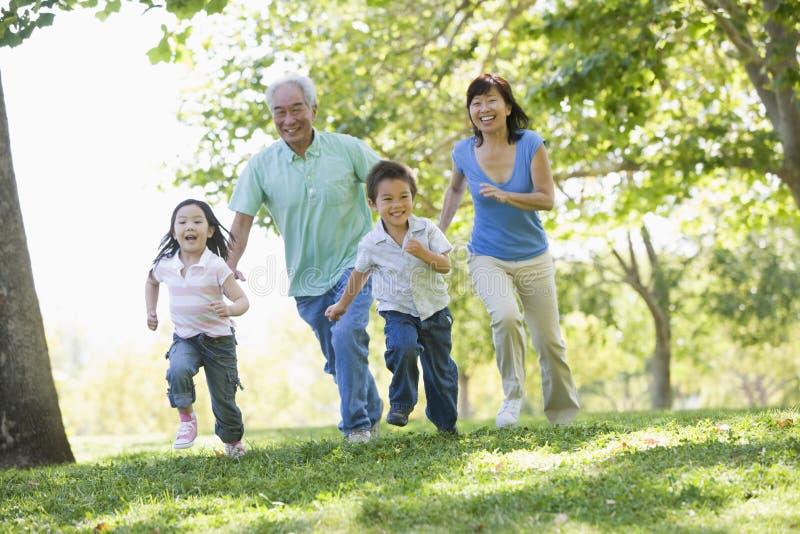 Großeltern, die mit Enkelkindern laufen lizenzfreies stockbild