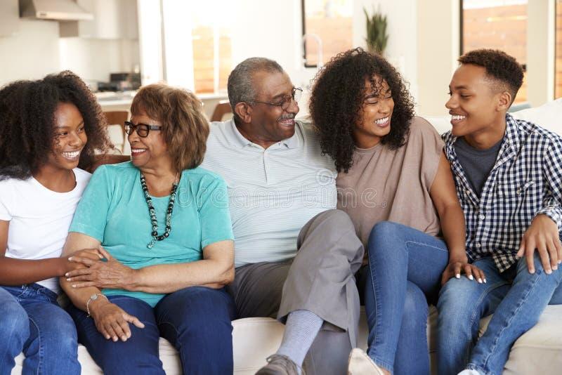 Großeltern, die sich zu Hause mit ihren jugendlich und jungen erwachsenen Enkelkindern entspannen lizenzfreie stockfotos
