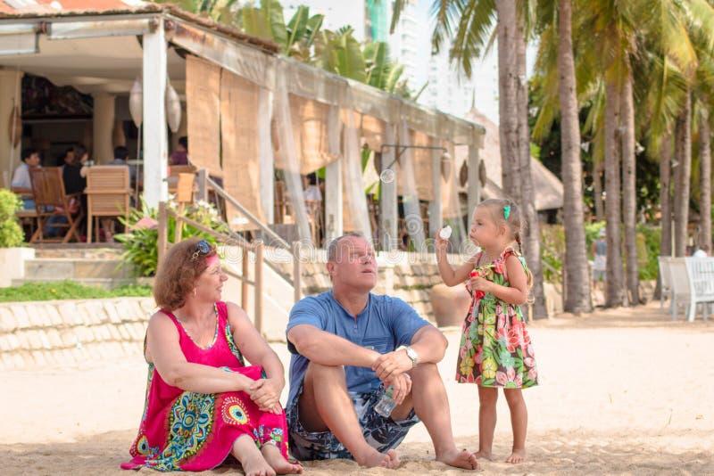 Großeltern, die Tag mit Enkelin beim Schlag von Seifenblasen auf dem Strand nahe dem Meer genießen lizenzfreies stockfoto