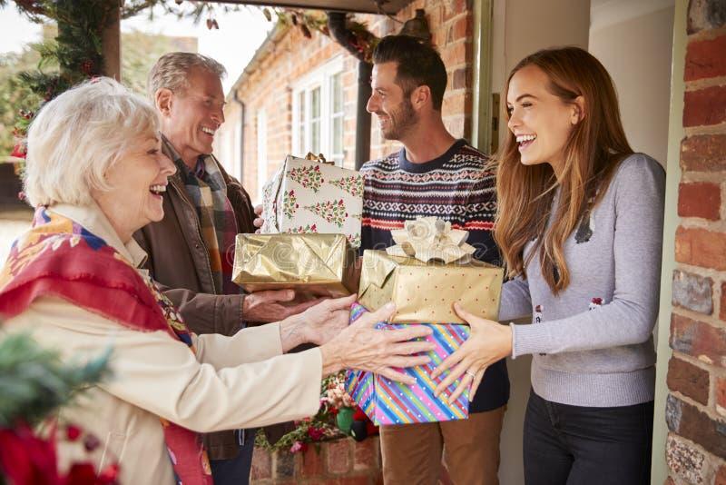 Großeltern, die von der Familie gegrüßt werden, wie sie für Besuch am Weihnachtstag mit Geschenken ankommen lizenzfreies stockfoto