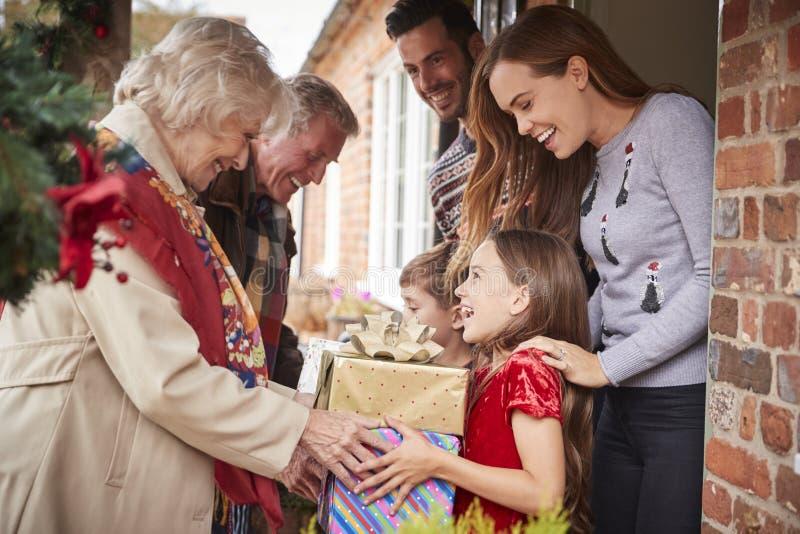Großeltern, die von der Familie gegrüßt werden, wie sie für Besuch am Weihnachtstag mit Geschenken ankommen stockbild
