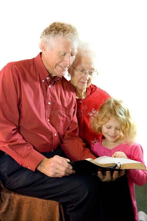 Großeltern, die zum Enkelkind lesen. lizenzfreies stockfoto