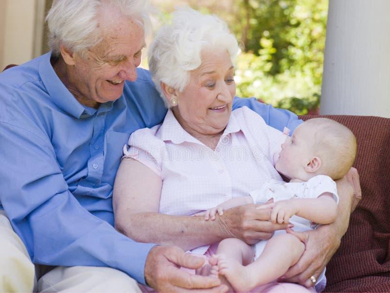Großeltern draußen auf Patio mit Schätzchen lizenzfreie stockbilder