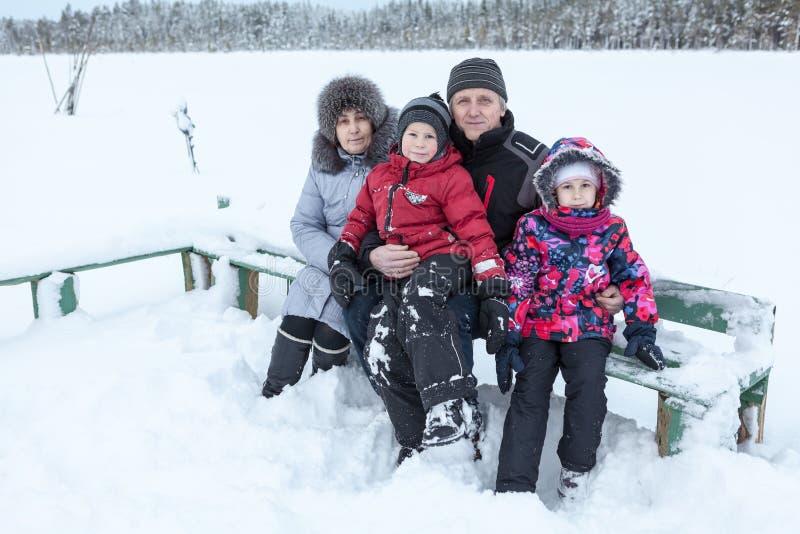 Großeltern gehen mit ihren Enkelkindern auf dem gefrorenen See und zusammen sitzen auf Holzbank lizenzfreie stockfotografie