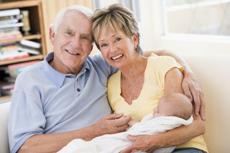 Großeltern im Wohnzimmer mit Schätzchen lizenzfreies stockbild