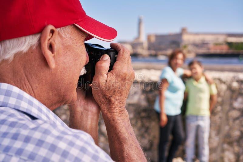 Großeltern mit dem Jungen-Familienurlaub-Großvater, der Foto macht lizenzfreie stockfotografie