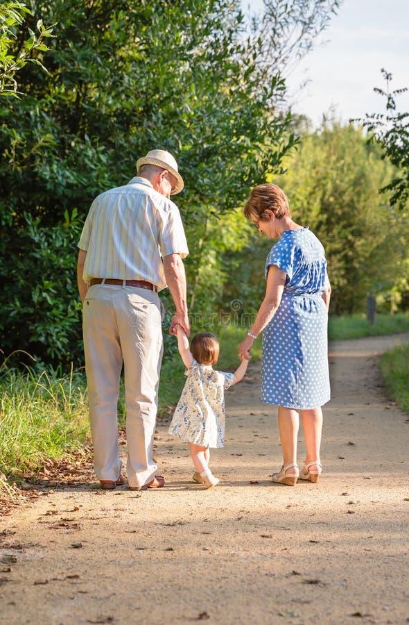 Großeltern und Babyenkelkind, das draußen geht stockfotografie