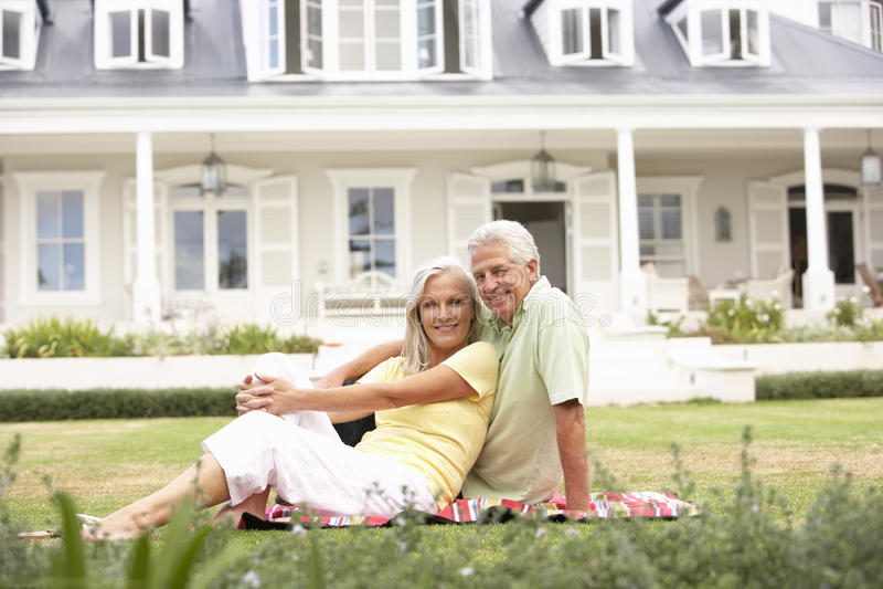 Großeltern und Enkelkinder, die außerhalb des Hauses auf Rasen sitzen lizenzfreies stockbild