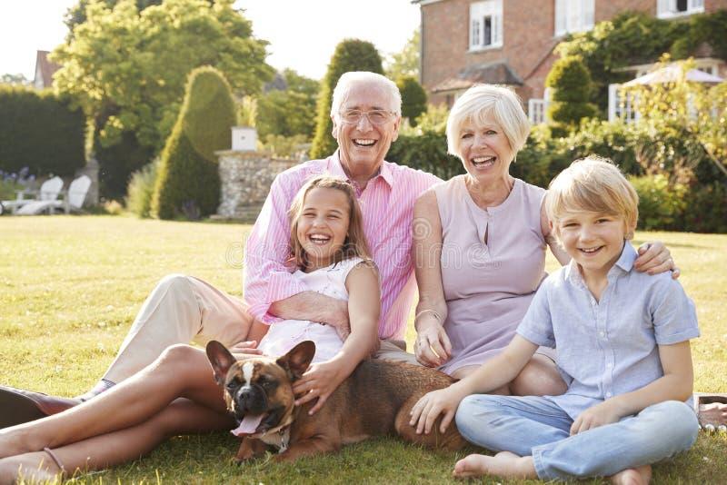 Großeltern und Enkelkinder, die im Garten mit Hund sitzen stockfotografie