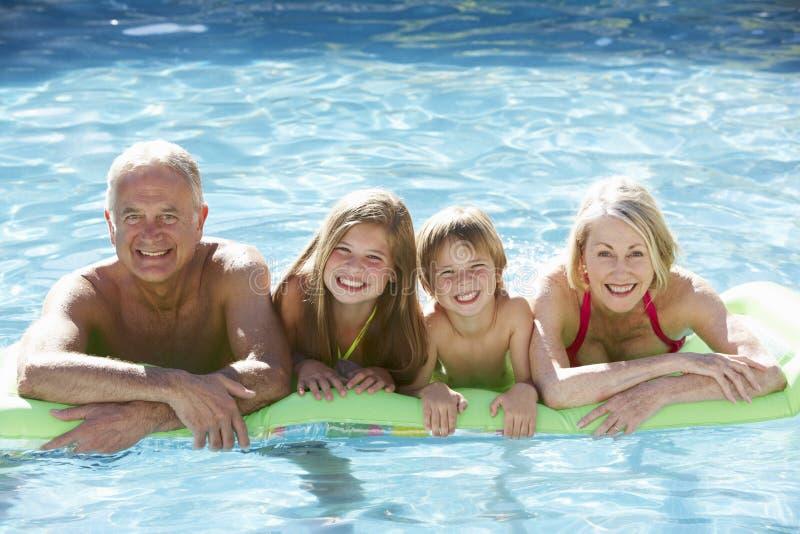 Großeltern und Enkelkinder, die sich zusammen im Swimmingpool entspannen lizenzfreies stockbild