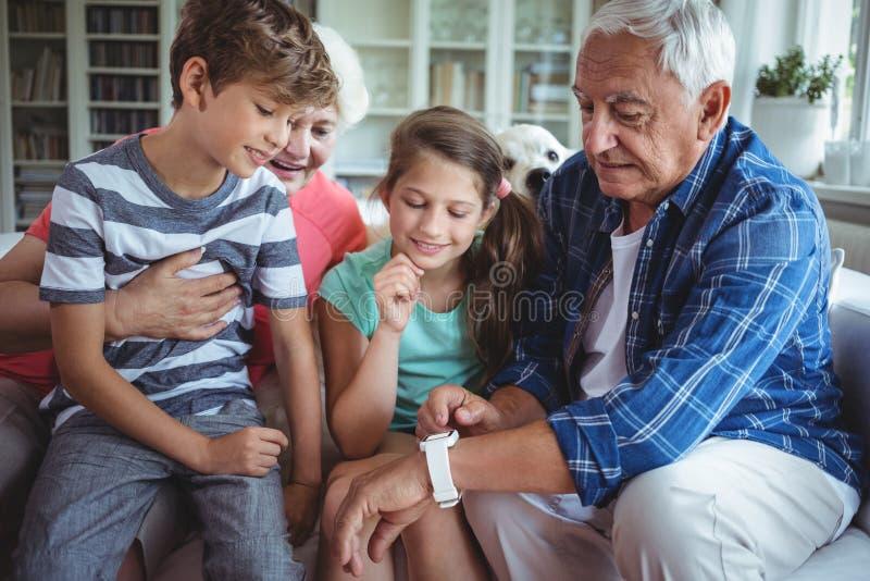 Großeltern und Enkelkinder, die smartwatch im Wohnzimmer betrachten stockfotografie