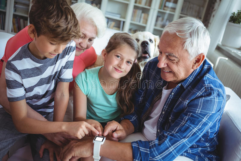 Großeltern und Enkelkinder, die smartwatch im Wohnzimmer betrachten lizenzfreies stockfoto