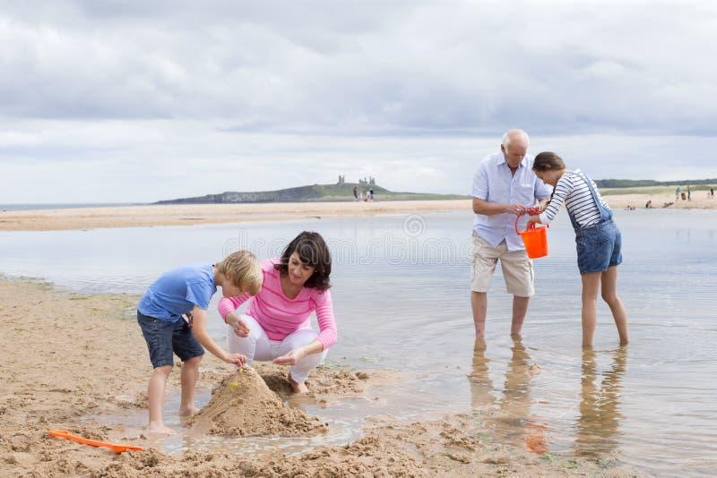 Großeltern und Enkelkinder, die am Strand spielen lizenzfreies stockbild