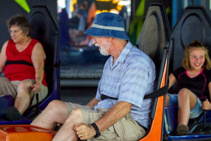 Großeltern und Grandaughter-Fahrautoskooters an einer Unterhaltung P stockfotografie