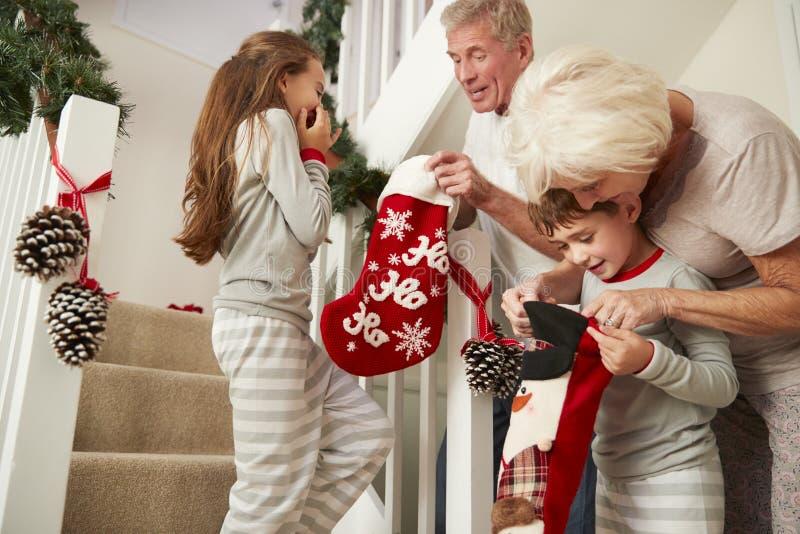 Großeltern, welche die aufgeregten Enkelkinder tragen die Pyjamas laufen hinunter die Treppe hält Strümpfe auf Weihnachtsmorgen g stockfotografie