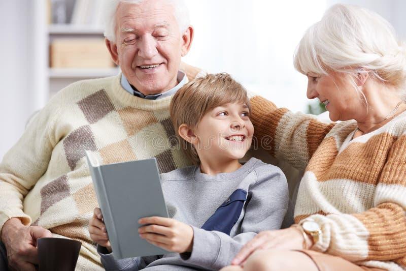 Großelternlesebuch mit Enkel lizenzfreies stockbild