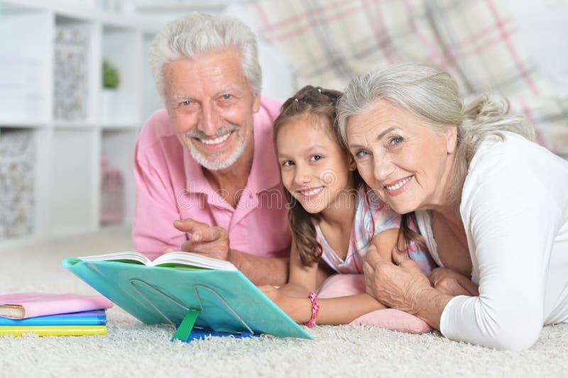 Großelternlesebuch mit kleiner Enkelin lizenzfreies stockfoto