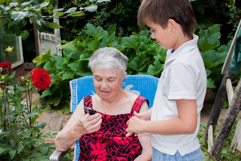 Großenkel der Urgroßmutter unterrichtet Kontakt stockbild