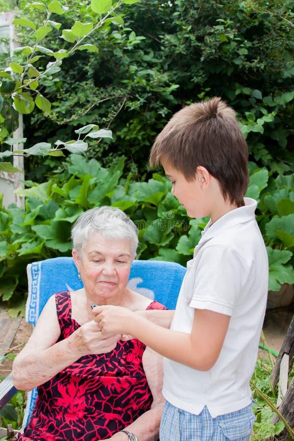 Großenkel der Urgroßmutter unterrichtet Kontakt stockfotos