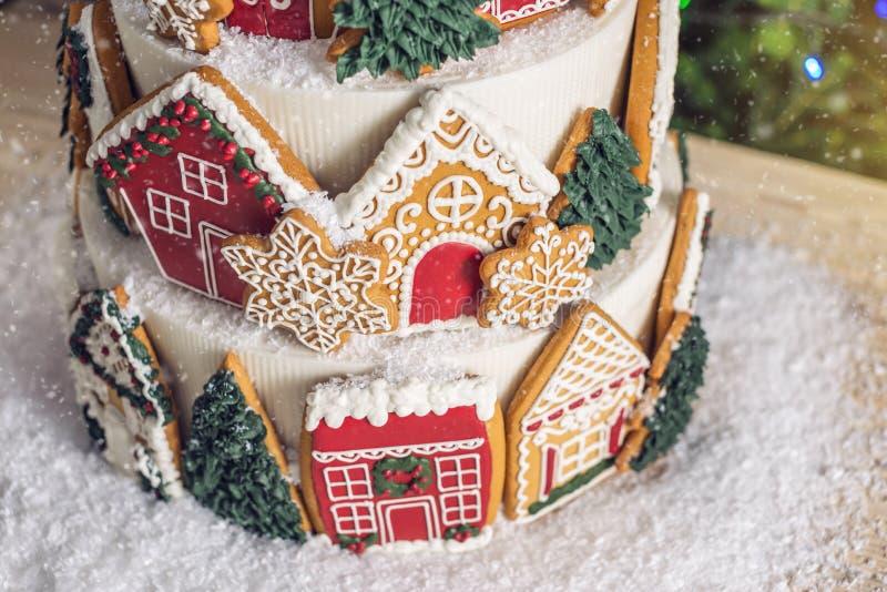Großer abgestufter Weihnachtskuchen verziert mit Lebkuchenplätzchen und ein Haus auf die Oberseite Baum und Girlanden im Hintergr stockfotos