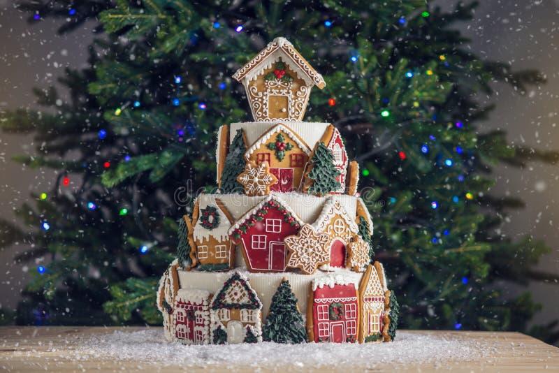 Großer abgestufter Weihnachtskuchen verziert mit Lebkuchenplätzchen und ein Haus auf die Oberseite Baum und Girlanden im Hintergr lizenzfreie stockfotos