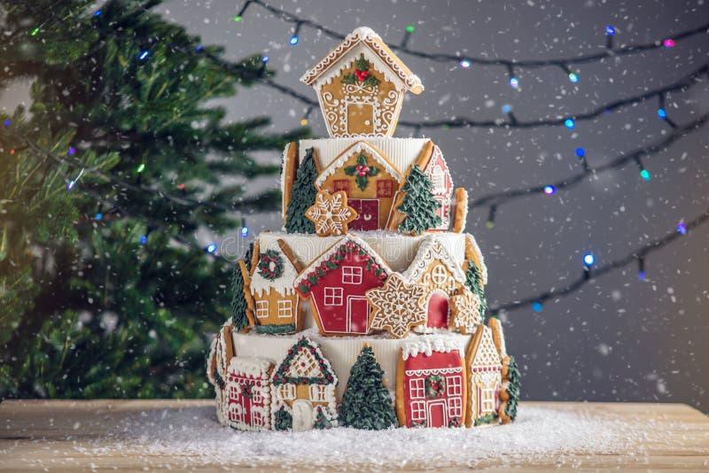 Großer abgestufter Weihnachtskuchen verziert mit Lebkuchenplätzchen und ein Haus auf die Oberseite Baum und Girlanden im Hintergr stockfoto