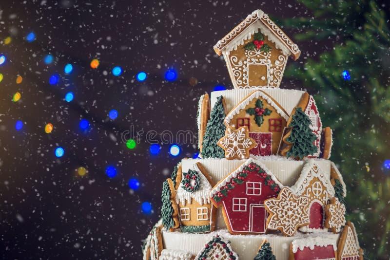 Großer abgestufter Weihnachtskuchen verziert mit Lebkuchenplätzchen und ein Haus auf die Oberseite Baum und Girlanden im Hintergr stockfotografie
