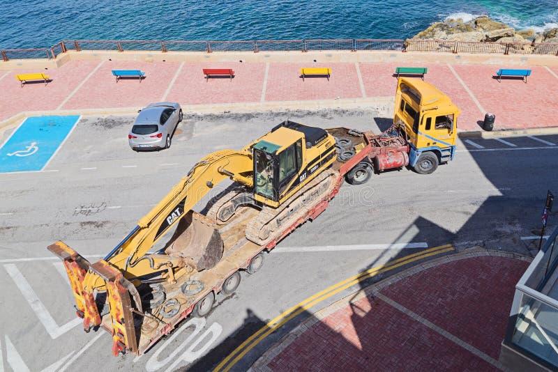Großer Anhänger transportiert Bagger stockbilder