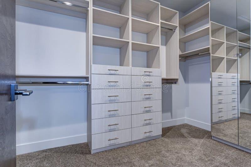 Großer begehbarer Schrank mit weißen Regalen, Fächer lizenzfreie stockbilder