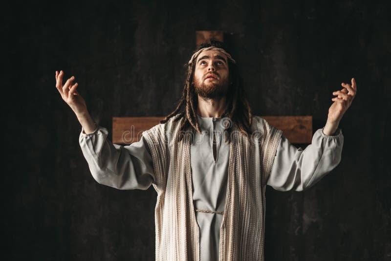 Großer betender Märtyrer, Kreuz auf schwarzem Hintergrund lizenzfreie stockfotos