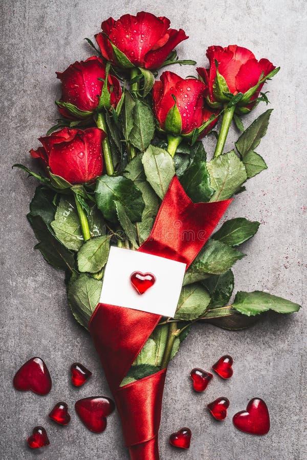 Großer Blumenstrauß der roten Rosen mit Schleifen- und Grußkarte mit Herzen, Draufsicht Rot stieg auf weißen Hintergrund lizenzfreies stockfoto