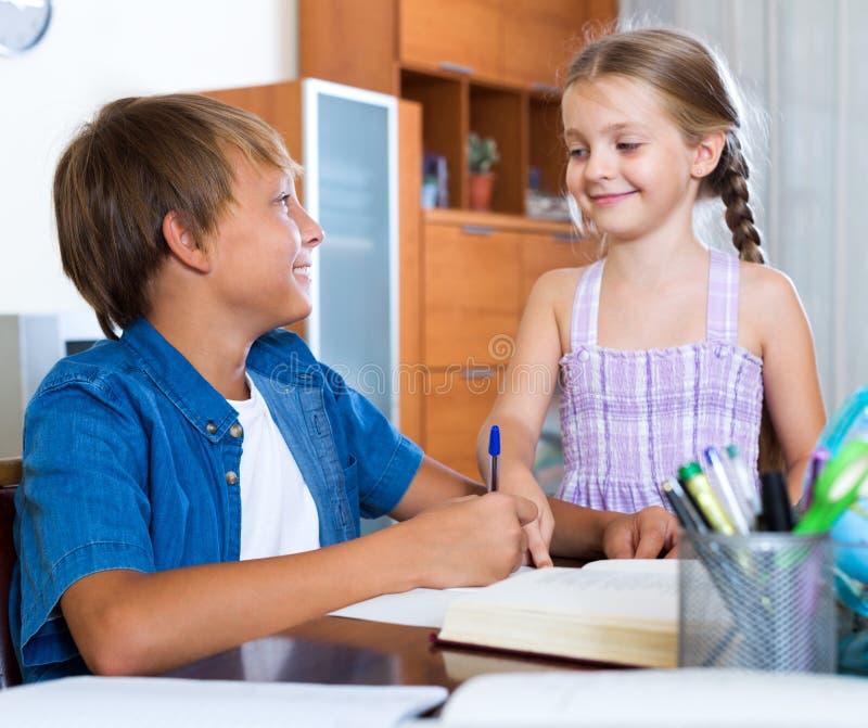 Schwester Hilft Bruder Mit Hausarbeit Stockfoto - Bild von