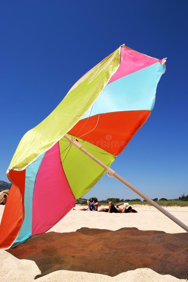 Großer bunter Regenschirm auf einem sonnigen Strand in Spanien lizenzfreie stockfotos