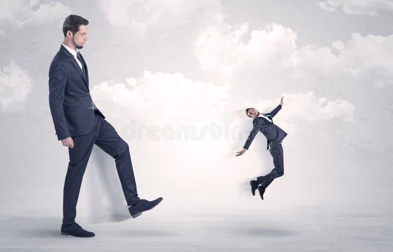 Großer Chef, der kleinen Angestellten tritt lizenzfreies stockfoto