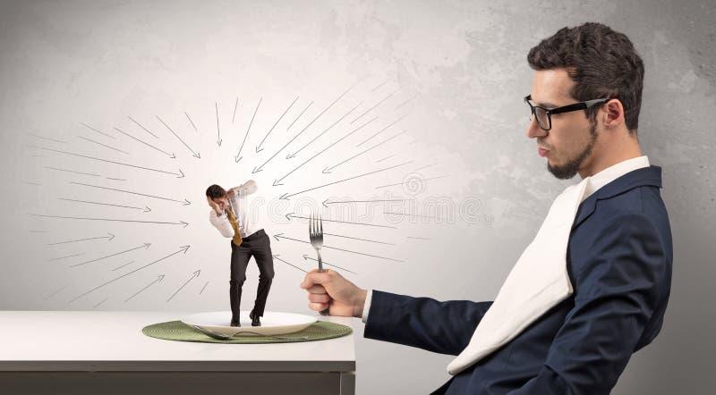 Großer Chef, der kleinen erschrockenen Angestellten isst lizenzfreie stockfotografie