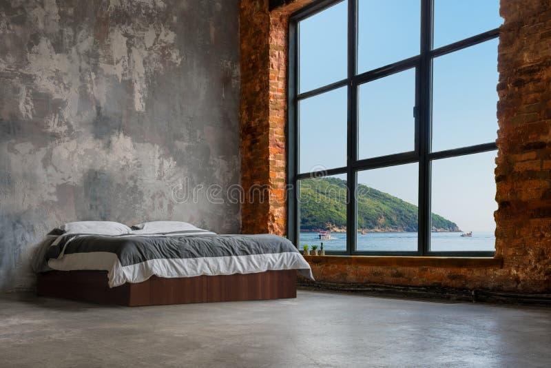 Großer Dachboden-Innenraum mit Bett und Meer und Berge im Fenster stockbilder